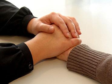 Zwei Hände halten eine andere Hand