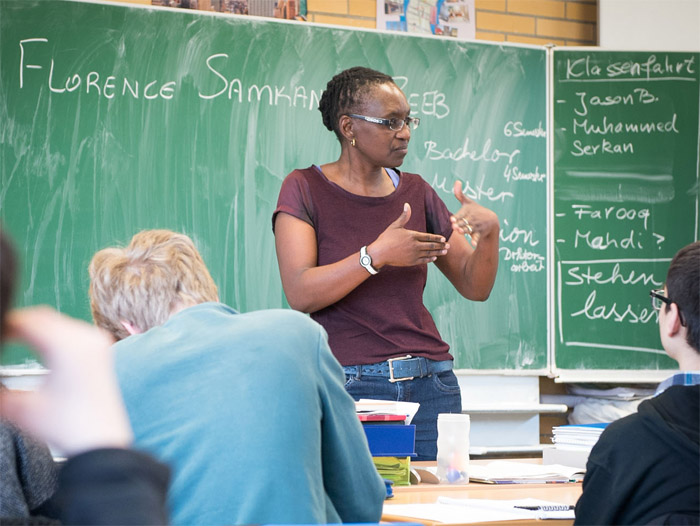 Klasse-Frauen: Eine junge Frau spricht vor einer Schulklasse