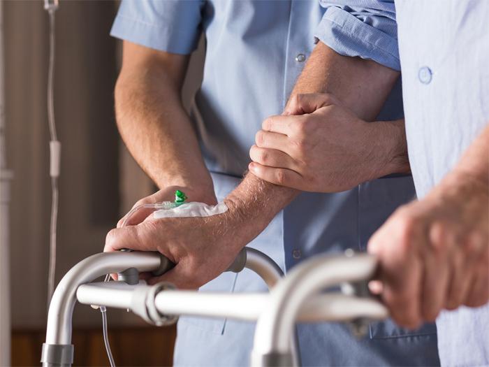 Pflegeberufe, Mann mit Gehilfe wird gestützt