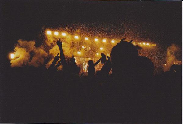 Menschen vor einer Bühne bei Nacht