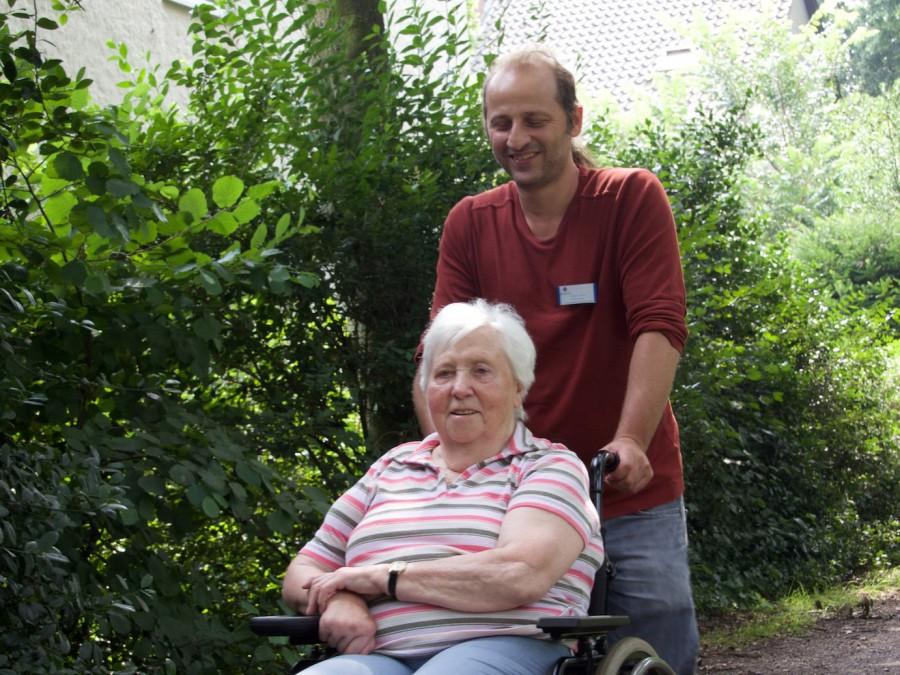 Seniorenbetreuer , Junger Mann schiebt alte Dame im Rolli