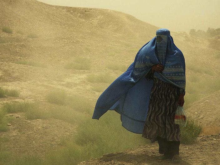 Frau mit Burka im Sandsturm