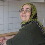 Frau mit Kopftuch an einem Spülbecken