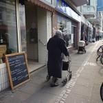 Eine alte Frau mit Rollator auf Fußweg