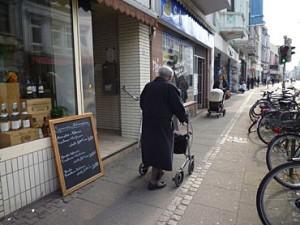 Ein älterer Herr mit Rolly auf einem Fußgängerweg.
