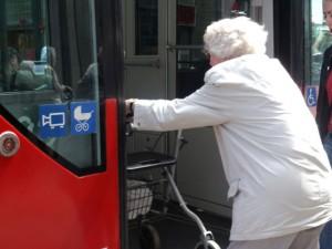 Alte Dame steigt mit Rollator in eine Straßenbahn