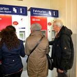 Eine Automatenhelferin zeigt einem Ehepaar, wie man Tickets am Automaten kauft.