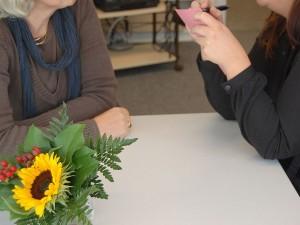 Eine ältere Dame und eine jüngere sitzen sich gegenüber, die junge notiert etwas auf einem Zettel. Im Vordergrund stehen Blumen.