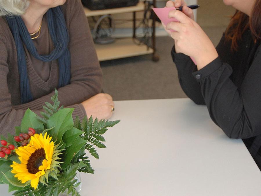 Unterstützung für Geflüchtete. Eine Ältere und eine Jüngere sitzen sich gegenüber, die junge notiert etwas auf einem Zettel.