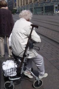 Frau sitzt auf Rollator