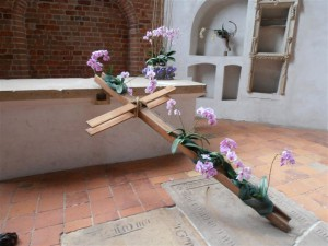 Holzkreuz geschmückt mit Blumen