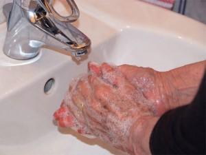 Eingeseifte Hände unter dem Wasserhahn