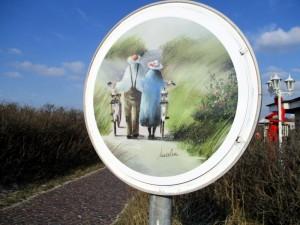 Verkehrsschild mit Fahrrad schiebenden Senioren