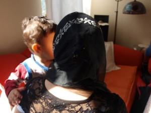 Frau mit Kopftuch hält Kind auf dem Arm