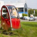 Frau in rotem Elektromobil