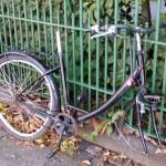 Kaputtes Fahrrad an einem Zaun