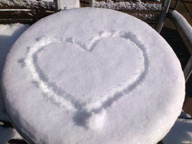 Caféhaustisch, schneebedeckt mit Herz
