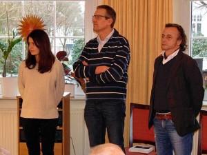 Eine Frau und zwei Männer stehen vor Publikum
