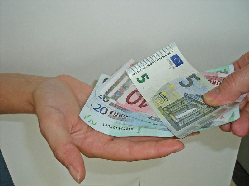Steuern zahlen, In eine offene Hand werden Geldscheine gezählt