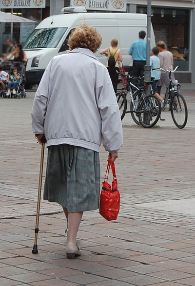 Altersarmut, Alte Frau mit Stock und Einkaufsbeutel