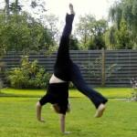 Leben ist Sport Frau turnt auf Rasen: Hände am Boden Füße in der Luft