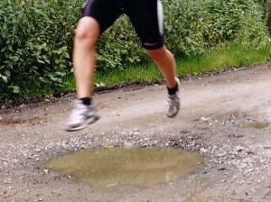 Joggerin springt über eine Pfütze
