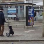 Altersarmut, Mann mit Shopper an einer Haltestelle