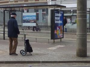 Mann mit Shopper an einer Haltestelle