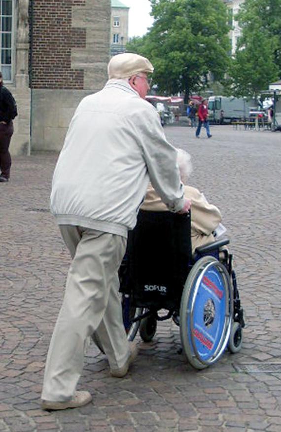 Reiseassistenz, Mann schiebt einen Rollstuhl