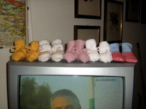 Aufgereihte babyschuhe auf einem Fernseher
