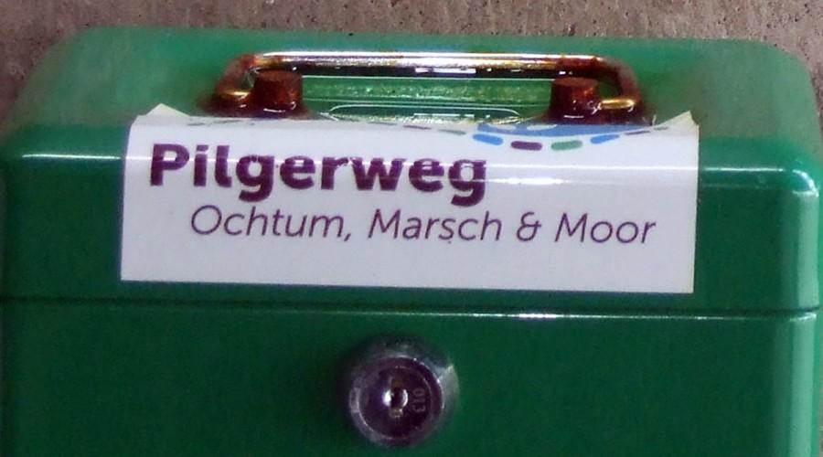 """Grüne Handkasse mit Aufschrift """"Pilgerweg"""""""