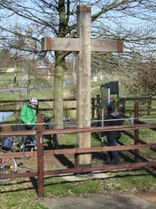 Zwei RadfahrerInnen unter einem Holzkreuz