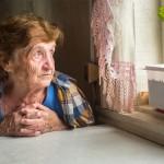 Gewalt in der Pflege, Alte Frau sitzt alleine vor einem Fenster