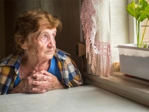 Alte Frau sitzt alleine vor einem Fenster