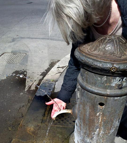 Eine Frau trinkt aus einem Brunnen