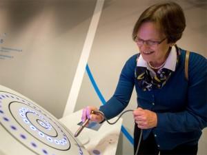 Facetten des Alters, Frau mit großer Scheibe und elektronischem Stift