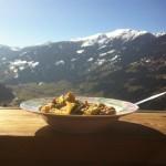 Teller mit Speise vor Alpenpanorama