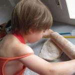 Kind mit Nudelholz und Teigklumpen