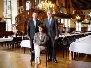 Stuhlpatenschaft Eine sitzende Frau hinter der zwei Männer stehen