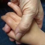 Alte Hand hält Kinderhand