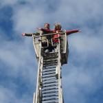 Zwei Frauen am Ende einer hohen Leiter vor blauem Himmel