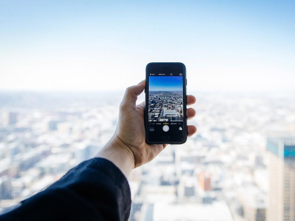 Hand beim Fotografieren einer Großstadt