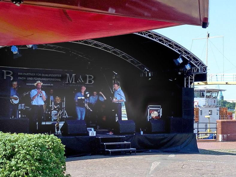 Musikband auf Bühne vor Hafenkulisse