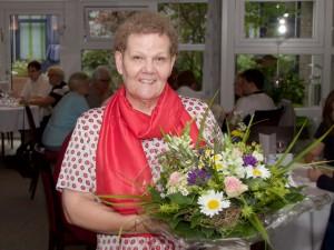 Nach 44 Berufsjahren in den Ruhestand, Frau mit Blumenstrauß