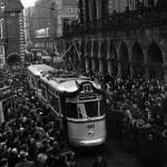 Historisches Bild mit Sambawagen und einer Menschenmenge, die vor dem Rathaus für eine neue Bahn Spalier steht.