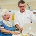 """Seniorenmesse """"InVita"""" Mann erklärt einer Seniorin ein Tablet"""