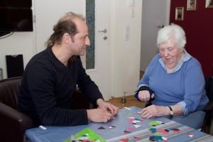 Junger Mann und alte Dame am Tisch