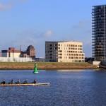 Ruderer auf einem Fluss vor Neubauten
