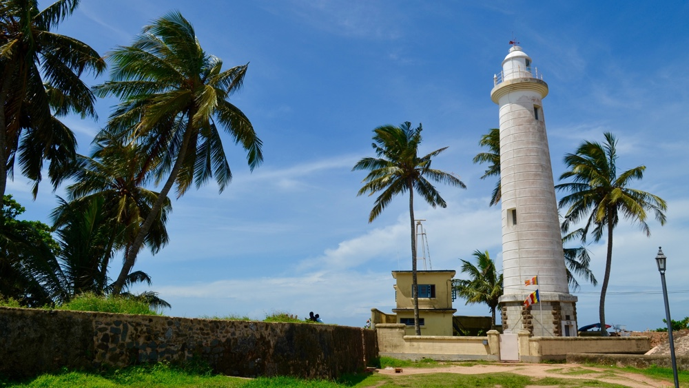 Landschaft mit Leuchtturm und Palmen