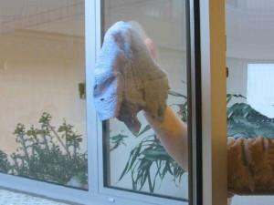 Hand beim Fensterputzen